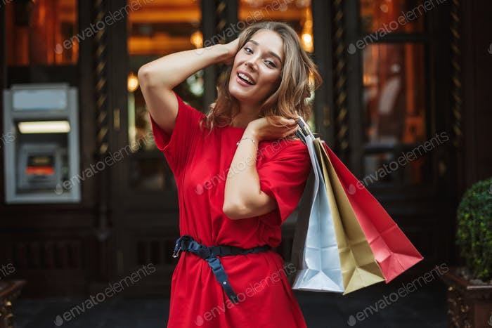 Young cheerful woman in red dress joyfully looking in camera whi