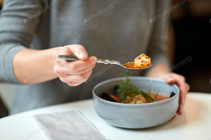 woman eating fish soup at cafe or restaurant
