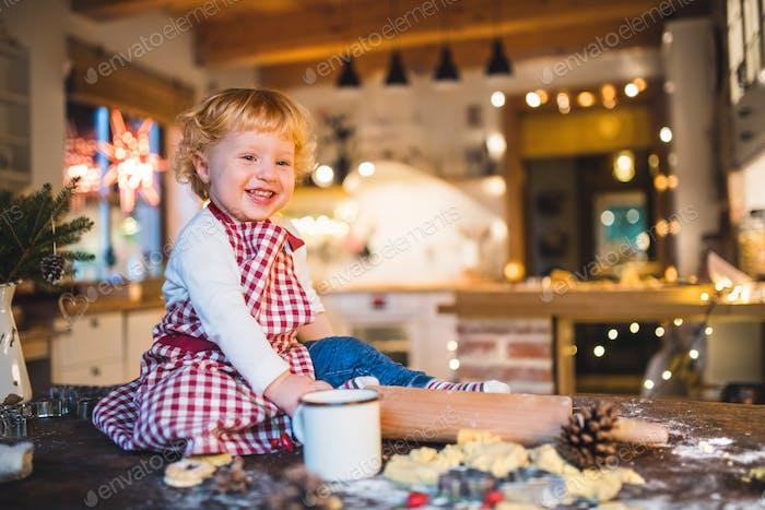 Kleinkind Junge machen Lebkuchenkekse zu Hause.