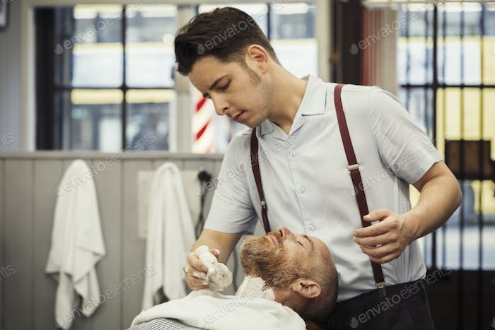 A customer sitting in the barber's chair, having a wet shave. A man using a shaving brush to lather