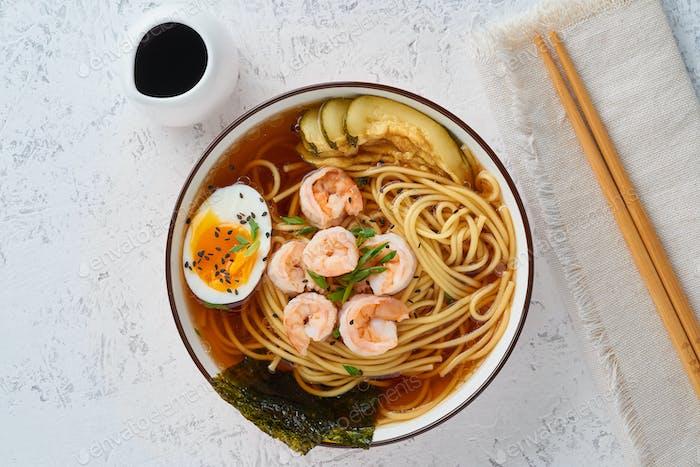 Asiatische Suppe mit Nudeln, Ramen mit Garnelen, Miso-Paste, Sojasauce. Tisch aus weißem Stein