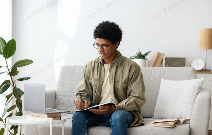 Distance education concept. Focused black student studying remotely on laptop computer at home