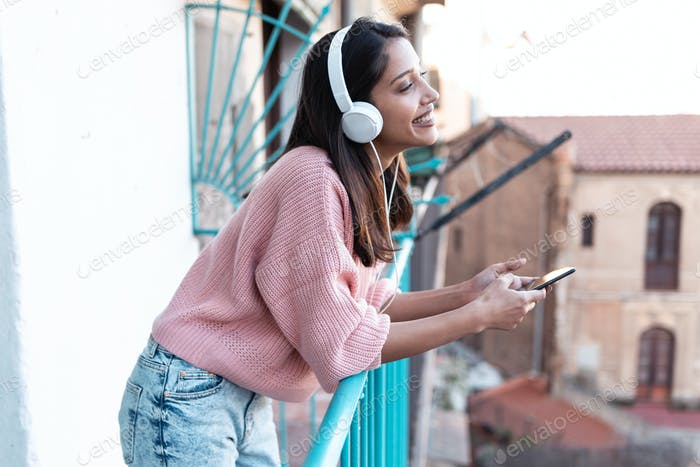 Pretty young woman listening to music with smartphone while standing on the rooftop at home.