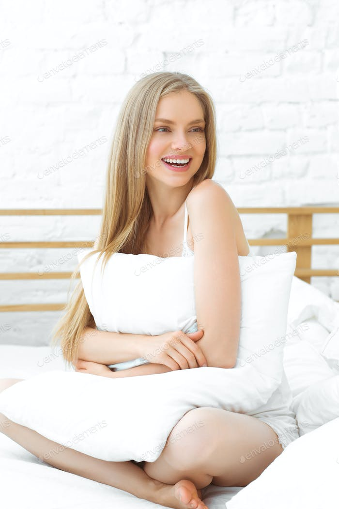 Woman bed home happy teeth smile lifestyle beautiful blonde female at sofa