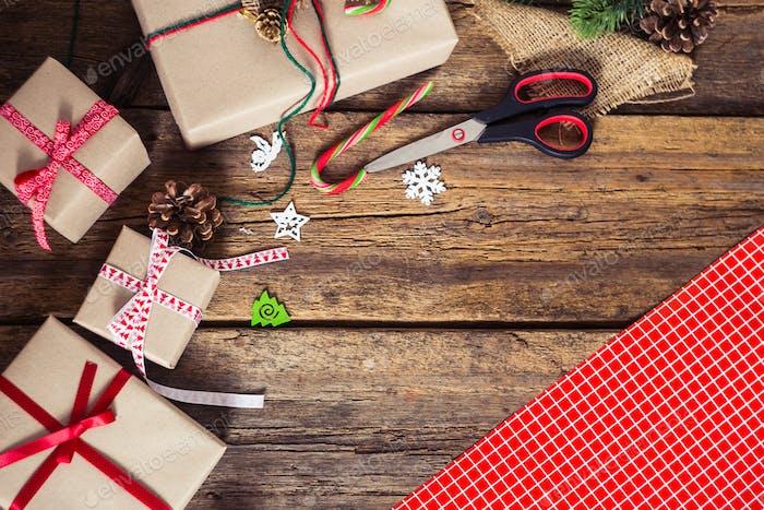 Weihnachtsgeschenke auf einem hölzernen Hintergrund mit Zuckerrohr, Tanne b