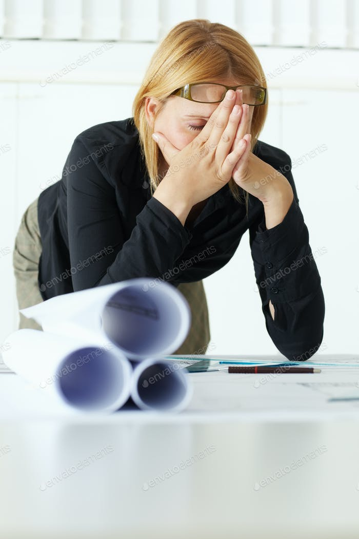 Tired And Upset Woman Working As Architect In Office