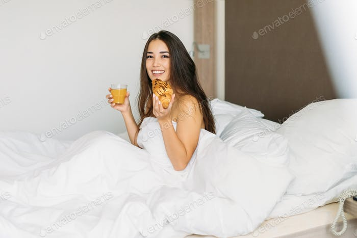 Young asian woman with long hair in having breakfast croissant and orange juice in bed