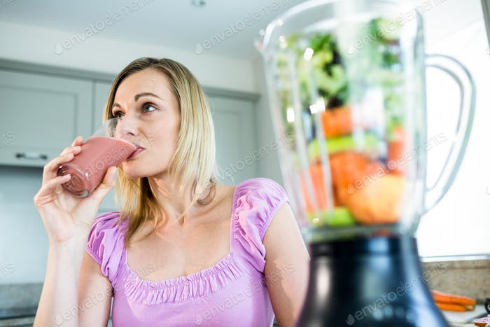 Blonde woman drinking a smoothie in the kitchen at home