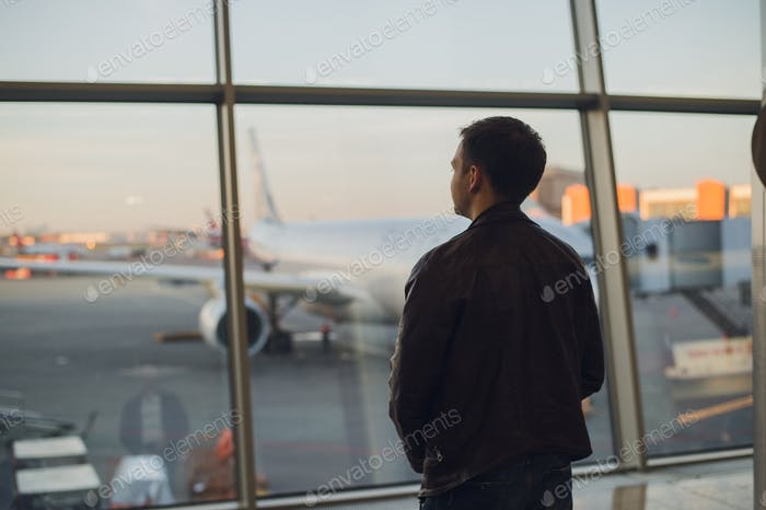 Young man is standing near window at the airport and watching plane before departure. Focus on his