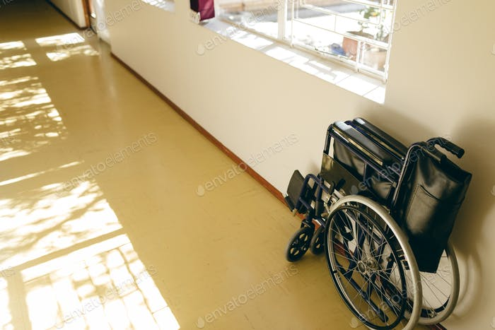 Front view of empty wheelchair against wall in corridor at retirement home