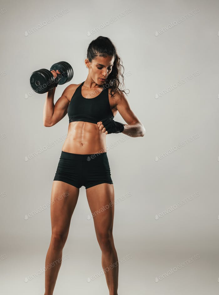 Strong woman doing shoulder press with dumbell
