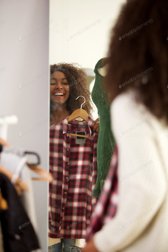 behind of happy young woman looking in a mirror and tries a checkered shirt