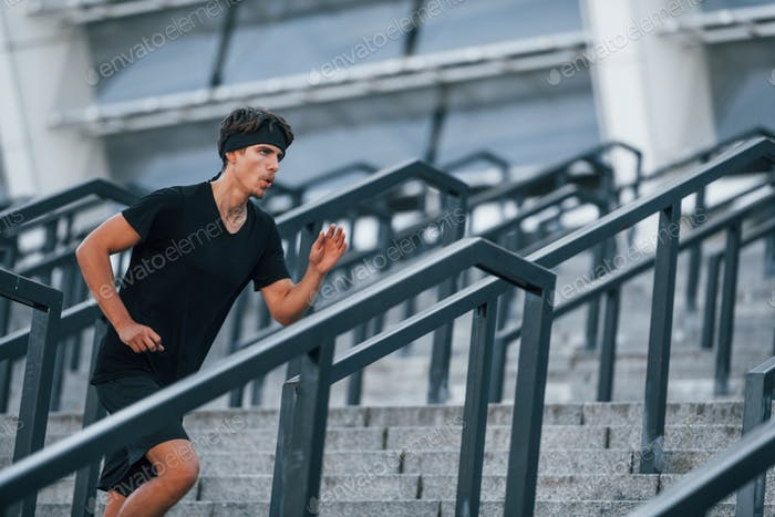 Running and jumping. Young man in sportive clothes have workout outdoors at daytime