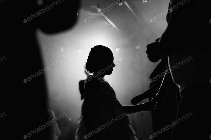silhouette of a child girl on the background of a bright spotlight