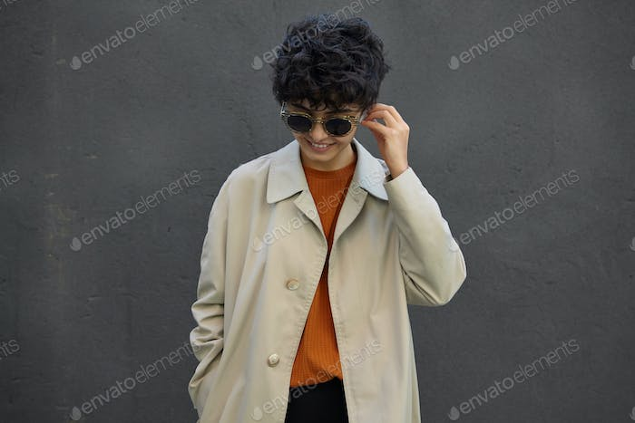 Outdoor shot of young curly dark haired lady with short haircut wearing beige trench coat