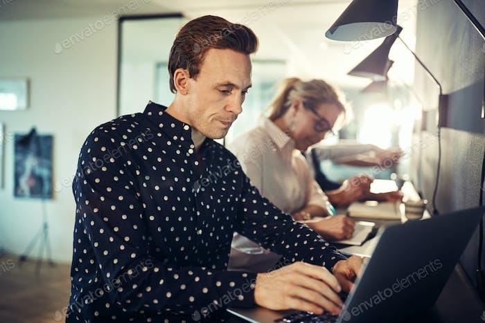 Designer arbeiten an einem Laptop mit Kollegen im Hintergrund