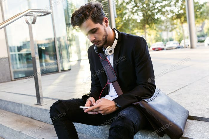 Handsome young man using his mobile phone in the street.
