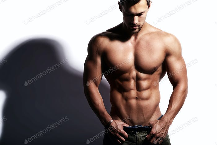 Portrait of young strong man with perfect sportive body posing in studio