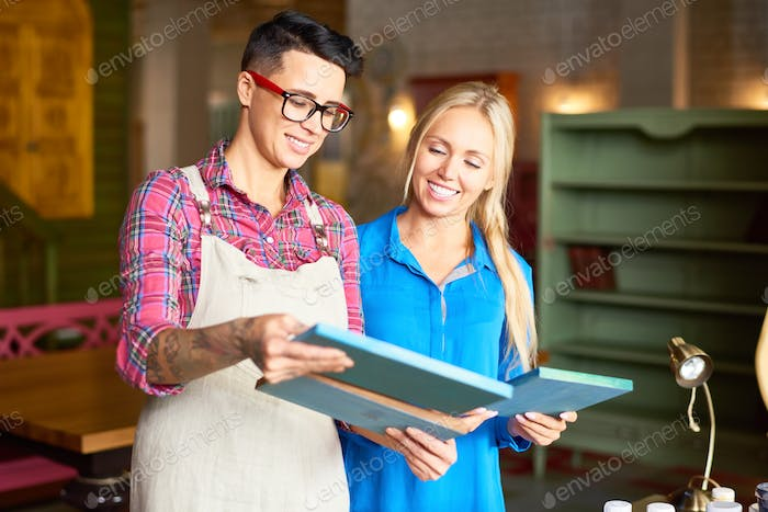 Two Women Choosing Pictures for Interior Decor