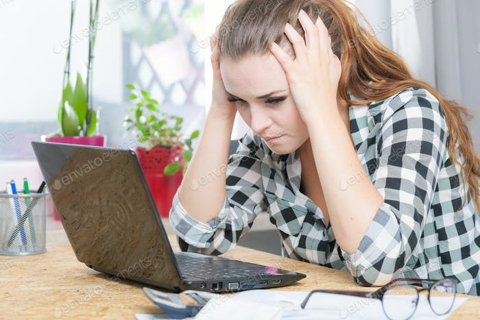 Desperate and worried woman calculating bills in home office