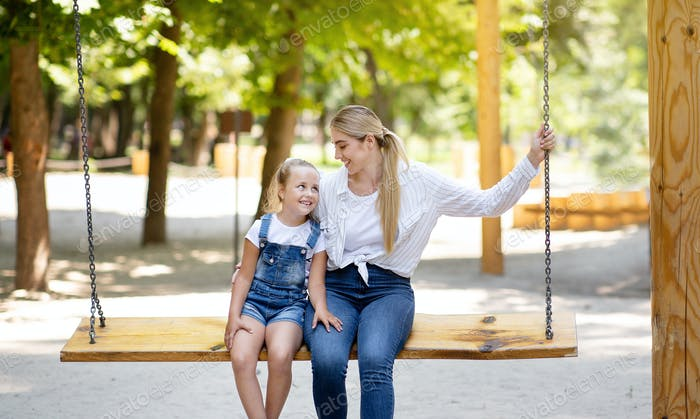 Mother And Little Daughter Swinging On Swings On Outdoor Playground