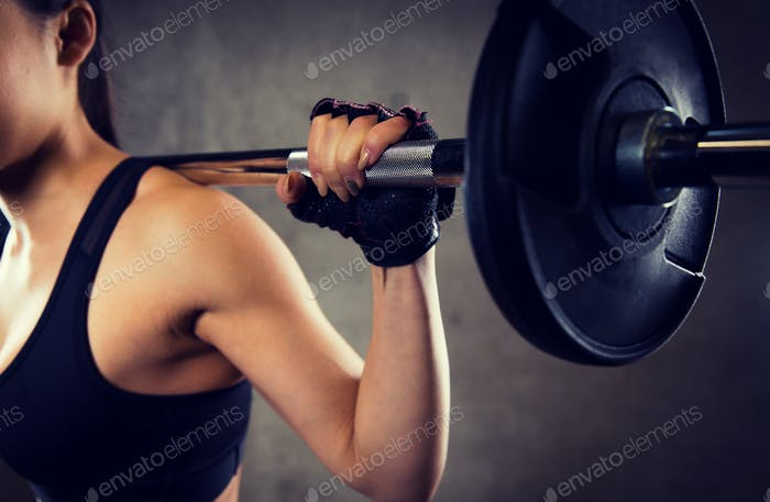 close up of woman with barbell in gym