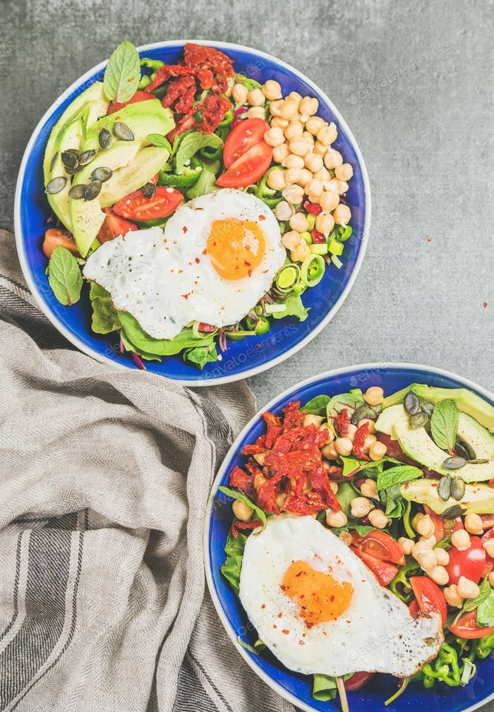 Healthy breakfast bowls with fried egg, chickpea sprouts, seeds, greens