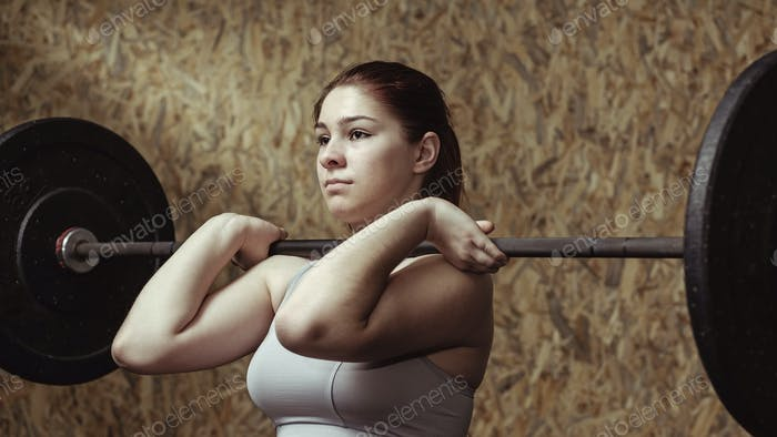 Young woman athlete working out with a barbell