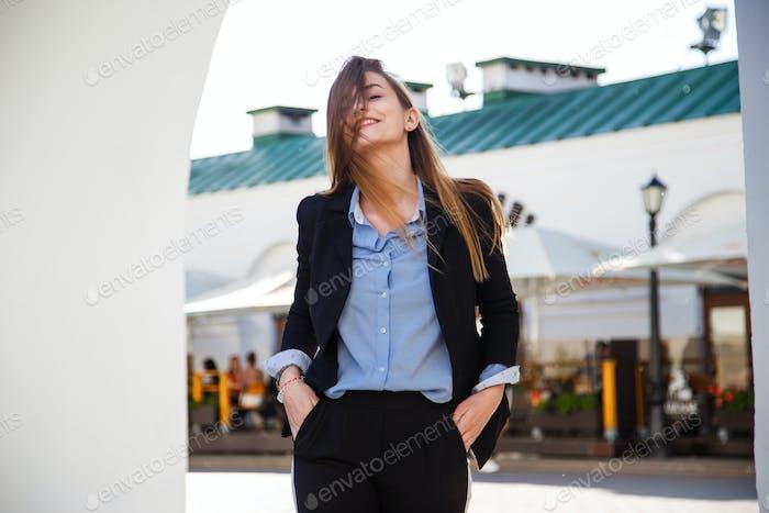 Sonriente joven Mujer Negocios Vertical en traje con hermoso pelo Largo