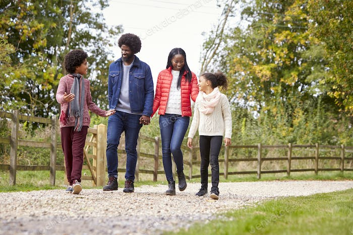 Mixed race family walking together on a country path, low angle