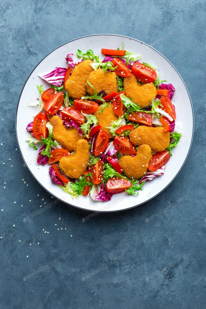 Chicken nuggets with salad. Fresh vegetable salad of tomatoes, lettuce and chicken nuggets