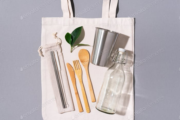Zero waste concept. Textile eco bags, glass jars and bamboo cutlery on grey background with copy