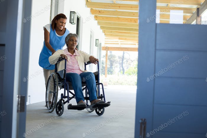 Female doctor pushing happy senior patient in wheelchair