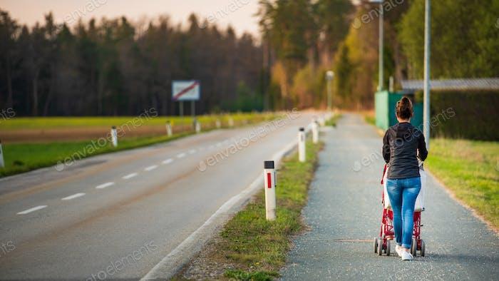 Junge Mutter und Kind im roten Kinderwagen wandert draußen in ländlicher Umgebung vor Sonnenuntergang