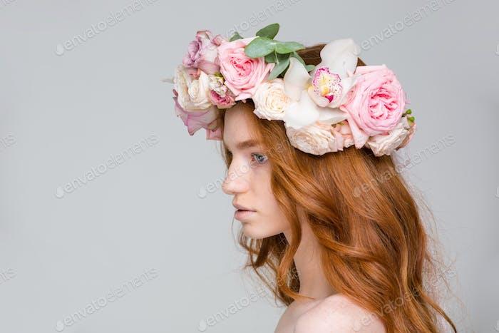 Profil der attraktiven jungen Frau in schönen Blumenkranz
