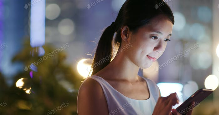 Frau Nutzung von Handy online in der Stadt bei Nacht
