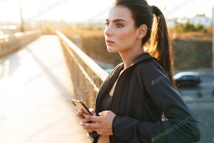Amazing young fitness woman using mobile phone outdoors.
