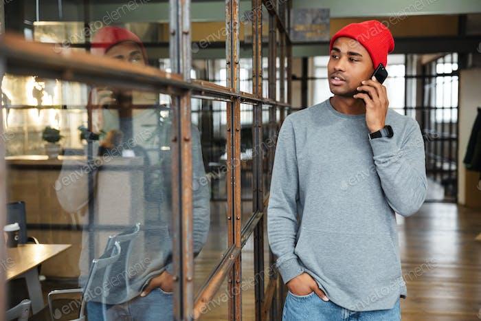 Bild von jungen afrikanischen amerikanischen Mann im Gespräch auf Handy im Büro