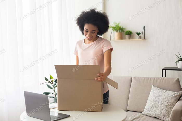 Smiling african american woman, near box and laptop