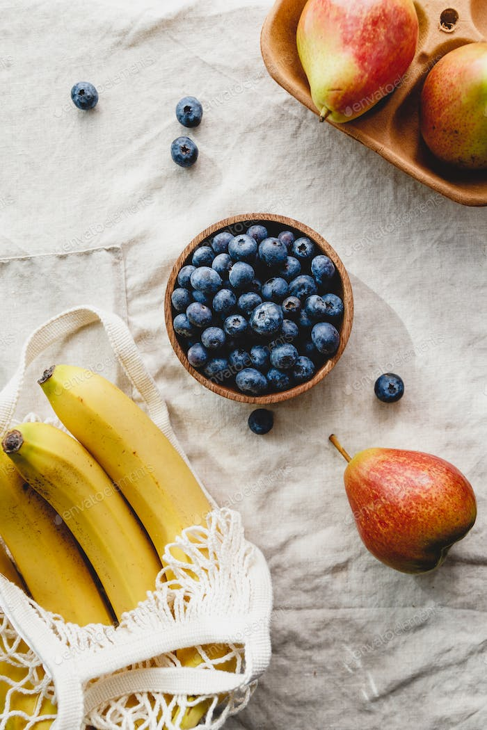 Bananas in a net bag, pears and blueberry on a linen napkin.