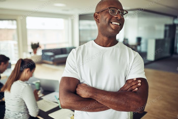 African businessman laughing with colleagues working in the background