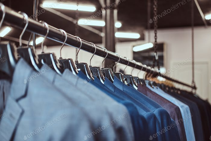 Photo of a rack with suit jackets in a menswear store.