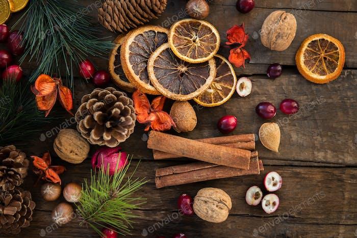 Xmas Symbols such as nuts, orange slices, tree branches, cranberries