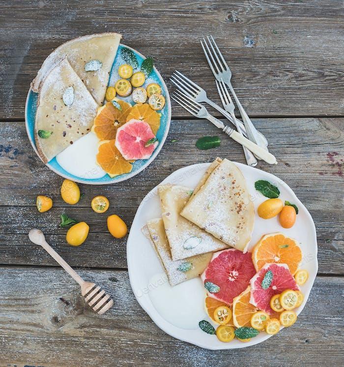 Spring vitamin breakfast set. Thin crepes or pancakes with fresh grapefruit, orange, kumquat, honey