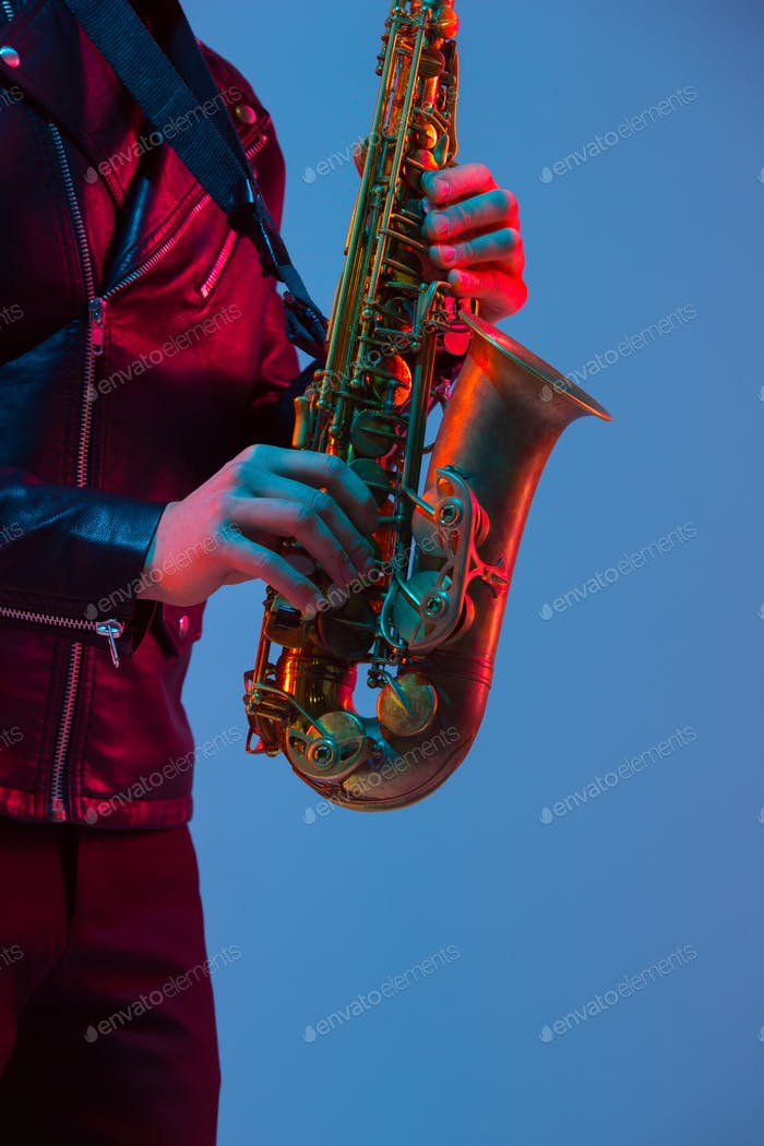 Young caucasian jazz musician playing the saxophone in neon light, close up