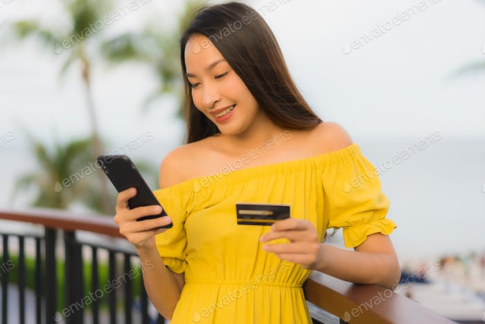 beautiful asian women show credit card with sea ocean view