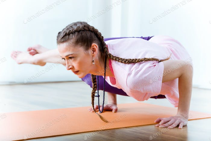 Beautiful young woman practicing yoga at home.