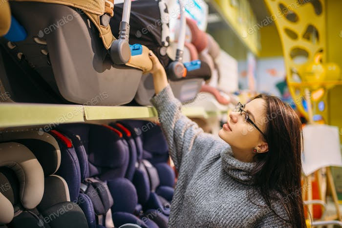 Pregnant woman choosing child car seat in store