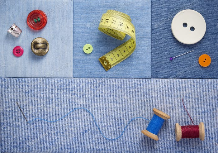sewing tools and accessories on jeans background