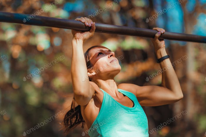 Woman doing pull-ups in the park